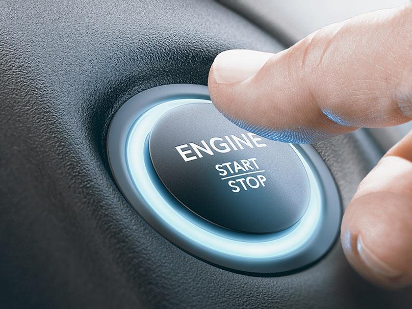 Un homme appuyant sur un bouton pour activer le Start and Stop sur une Peugeot 208.