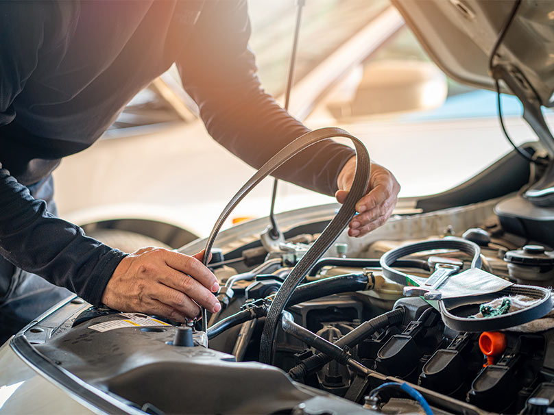 Un garagiste en train de changer la courroie de distribution sur une Peugeot 2008.