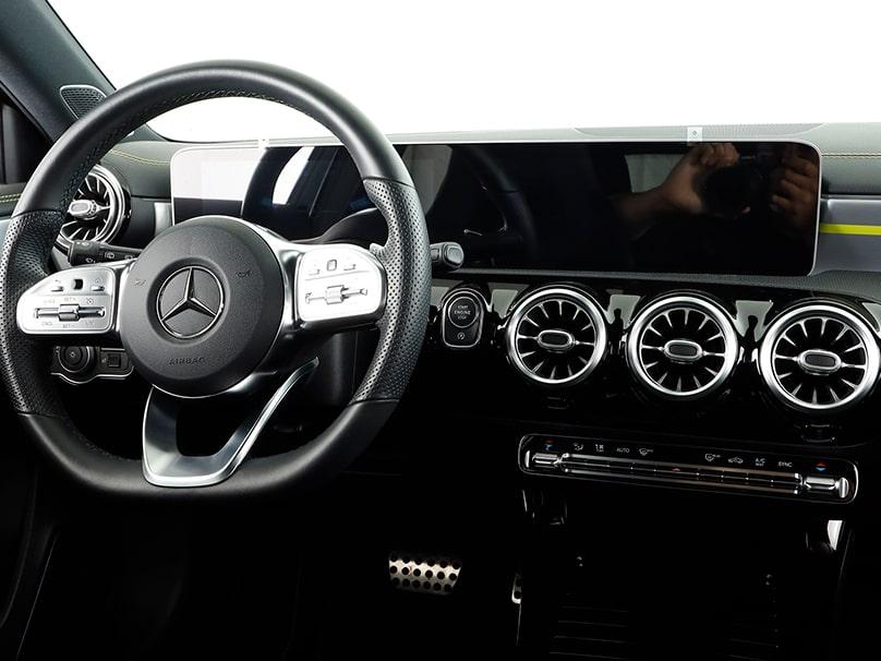 Zoom sur le poste de conduite d'une Mercedes et sur les palettes au volant.