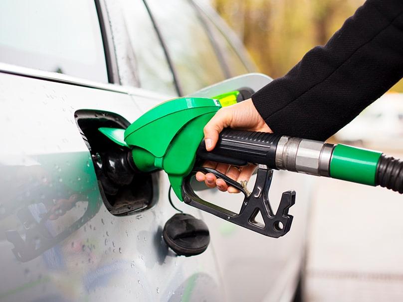 Une femme mettant de l'essence dans sa voiture.